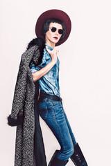 Glamorous fashion model in coat and stylish jeans clothes. Fashi