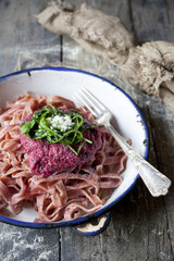 pasta with beetroot pesto, rocket and parmesan on plate