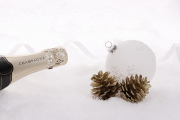 Champagne bottle in snow with christmas tree ball