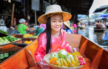 Child sit on the boat and hold the fruit basket