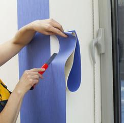 Woman cutting length of wallpaper
