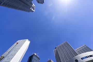 東京都庁と新宿高層ビル街を見上げる 快晴青空にふりそそぐ太陽