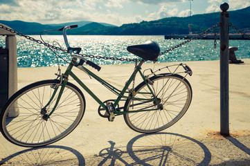 An old bicycle standing near a sea in Italy. Toned image.