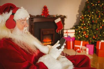 Santa claus listening music with his smartphone