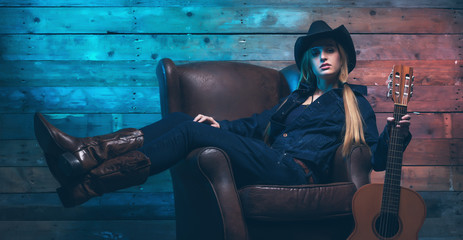 Cowgirl country singer with acoustic guitar. Sitting on leather