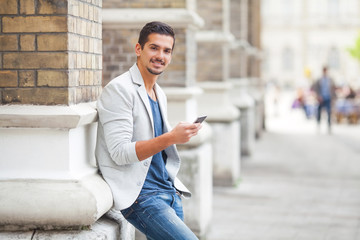 Young businessman using a smart phone on the street