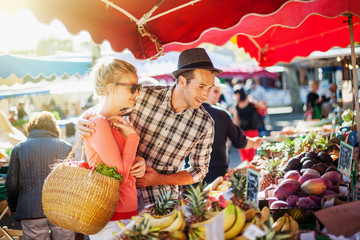 a young couple buying fruits and vegetables at a market