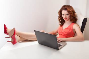 beautiful woman in pink dress at  table with laptop