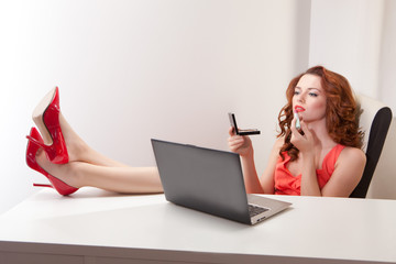 beautiful woman in pink dress at  table with laptop embellish