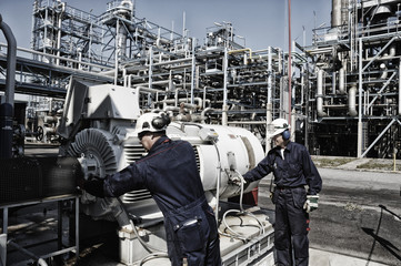 two workers with fuel-pump inside refinery industry