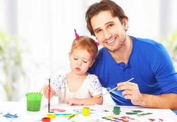 happy family father and child  daughter together draw paints