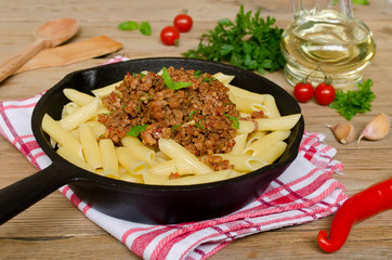 Pasta with Bolognese ragout on a wooden table
