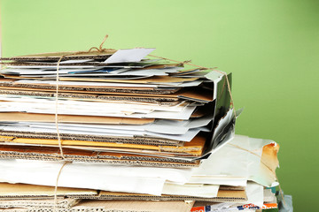 Big stack of papers on green background, close-up