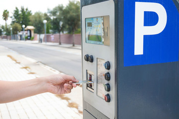 hand putting in credit card in a parking mete