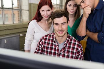 vier studenten schauen auf computer