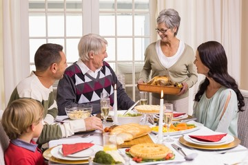 Grandmother holding turkey roast with family at dining table