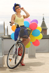 beautiful pin up with balloons on a bicycle