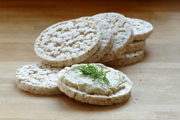 rice cakes, one with cream cheese and herbs on a wooden board