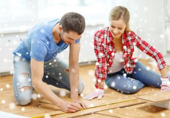smiling couple measuring wood flooring