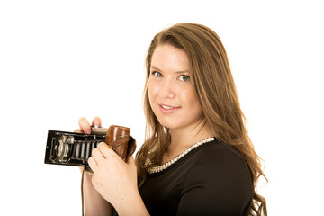 Woman looking into camera holding an antique camera