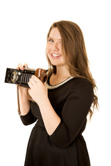 Pretty young woman photographer holding an antique camera smilin