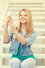 smiling female student with smartphone