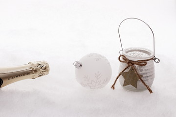 Christmas ball,  wind candle, champagne bottle in snow
