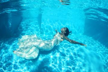 Fantasy bride underwater in a bird cage