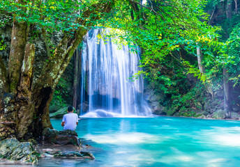 Wall Mural - A man look at waterfall while sitting under the tree