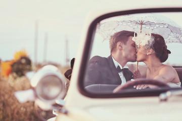 Bride and groom in a vintage car