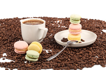 Coffee cup with macaroon and beans on a white background.