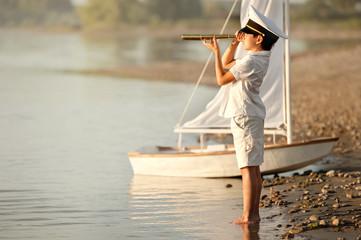 Boy captain looking through a telescope at the lake