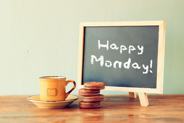 blackboard with the phrase happy monday next to cup of coffee an