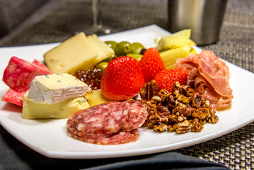 cheese, nut and meat plate with olives and strawberries