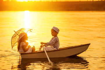 Boy with a girl floating on a boat rowed across the lake