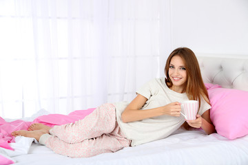 Young beautiful woman lying in bed with cup of hot drink