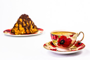 red flowered cup of tea on a background of a piece of cake