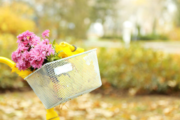Beautiful yellow bicycle in autumn park with bouquet of