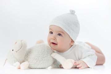 baby in white dress with a toy sheep