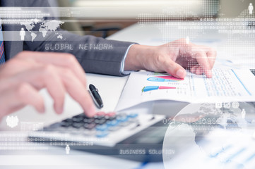 Business person using calculator against technology background