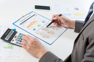Businessman analyzing report, business performance concept