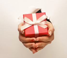 Hand breaking white paper showing gift box isolated