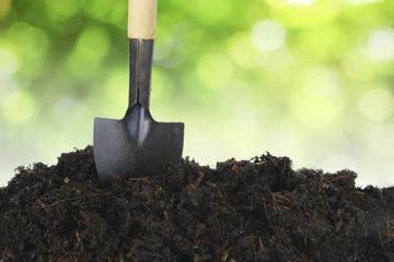 Soil with shovel and green bokeh