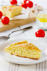 Cheese pie in a white plate with cherry tomatoes