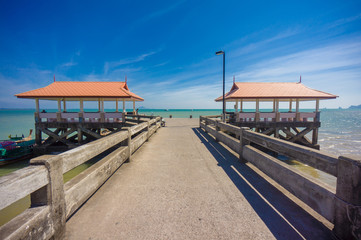 Long concrete pier on tropical beach with two canopy
