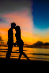 silhouettes of young loving couple on bright sunset sky and sea