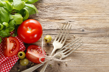 Italian cuisine: tomatoes, olives and basil leaves on wooden tab