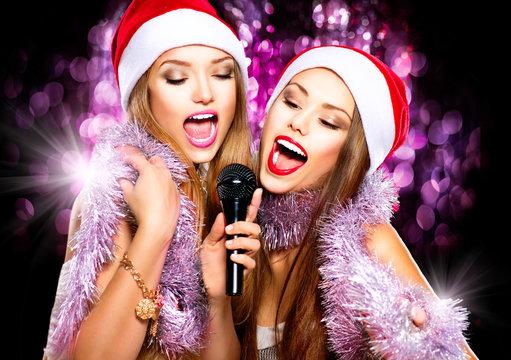 Christmas party, karaoke. Beauty girls in santa hats singing