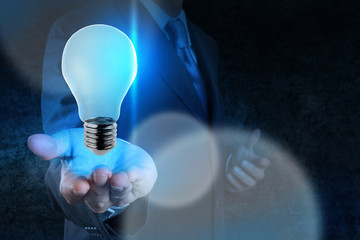 Businessman hand working with 3d light bulb of leadership conce