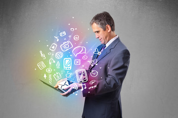 Businessman holding notebook with colorful hand drawn multimedia